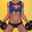 Постер, плакат: Female weightlifter in a Superman top