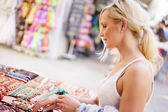 Cute blonde woman on holiday buying gifts — Stock Photo