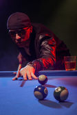 Fashionable pool player in a dark nightclub — Stock Photo