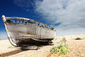 Wooden fishing boat left to rot and decay on the shingle beach at Dungeness, England, UK. — Stock Photo