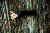 Thumb up shown by a person captive in prison — Stockfoto