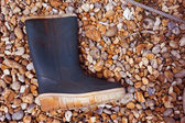 Old gumboot washed up on a stony seashore — Stock Photo