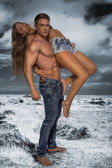 Hunky male carrying female model — Stock Photo