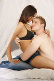 Loving couple sitting on a bed in a close embrace — Stock Photo
