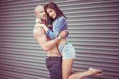 Shirtless man carrying female model — Stock Photo