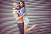 Shirtless man carrying female model — Stock Photo