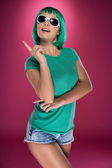 Trendy modern young woman pointing up — Stockfoto
