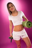 Fit woman carrying exercise equipment — Stock Photo