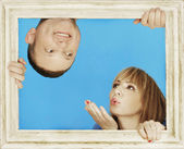 Couple Behind Wooden Frame on Sky Blue Background — Stock Photo