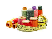 Multicolored thread spools and measurement tape.Isolated. — Stock Photo
