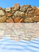 Taş duvar dalgalanma mavi su yansıtılıyor. — Stok fotoğraf