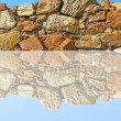 Old stone wall being reflected in water. — Stock Photo