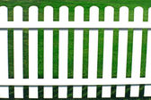 Green grass on other side behind a white fence. — Stock Photo