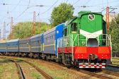 Green locomotive and blue passenger cars. — Stock Photo