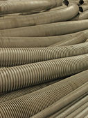 Various flexible metal hose in a warehouse. — Stock Photo