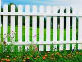 White fence on green grass with flowers. — Stock Photo