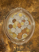 Golden oval photo frame with numismatic coins collection inside. — Stock Photo