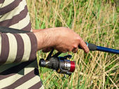 Hands of a fisherman with spinning rod on a river. — Stock Photo