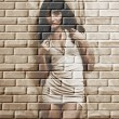 Cute brunette on a brick wall grunge background. — Stock Photo