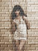 Cute brunette on a brick wall grunge background. — Stock Photo
