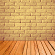Indoor background with yellow brick wall and wooden plank floor. — Stock Photo