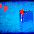 Stock Photo: Blue Valentines gift bag and red hearts on blue grungy backgroun