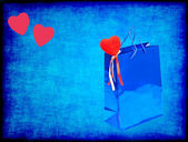 Blue Valentines gift bag and red hearts on blue grungy backgroun — Stock Photo