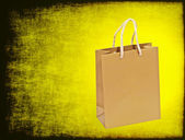 Golden shopping bag on a yellow grungy background. — Zdjęcie stockowe