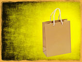 Golden shopping bag on yellow grungy background with frame borde — Stock Photo