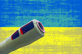 Artillery cannon against of destroyed Ukrainian flag.War in Ukra — Stock Photo