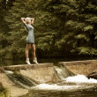 Beautiful Blonde Woman Standing near the Waterfall - Стоковая фотография