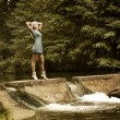 Beautiful Blonde Woman Standing near the Waterfall - Stockfoto