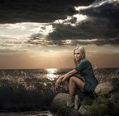 Schöne blonde frau sitzt nahe dem meer — Stockfoto