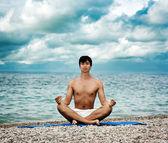 Uomo facendo yoga vicino al mare — Foto Stock