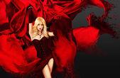 Mujer sexy con salpicaduras de seda roja — Foto de Stock