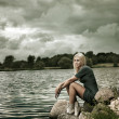 Beautiful Blonde Woman Sitting near the Water - Foto Stock
