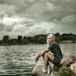 Beautiful Blonde Woman Sitting near the Water - Stock Photo