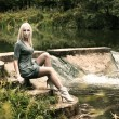 Beautiful Blonde Woman Sitting near the Waterfall - Stock Photo