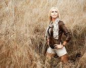 Blond kobieta pozowanie w polu. widok z tyłu — Zdjęcie stockowe