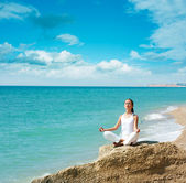 Woman Doing Yoga near the Sea — Stock Photo