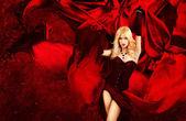 žena sexy blondýna fantazie s šplouchání červeného hedvábí — Stock fotografie