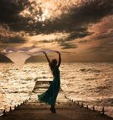 Vrouw in jurk met stof op zee — Stockfoto
