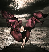 Blonde Woman with Waving Silk at Stormy Sea — Stock Photo