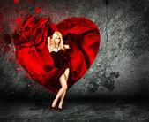 Vrouw met spatten hart op donkere achtergrond — Stockfoto
