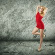 Beautiful Woman in Red Dress on Wall Background - Stock Photo