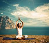 Donna facendo yoga presso il mare e le montagne — Foto Stock