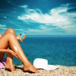 Tan Woman Applying Sunscreen on Legs — Stock Photo