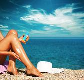 Tan женщина применять солнцезащитный крем на ноги — Стоковое фото