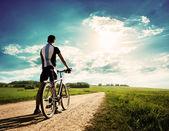 Hombre con una bicicleta en el fondo de la hermosa naturaleza — Foto de Stock