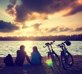 Couple avec bicyclettes relaxants au coucher du soleil — Photo